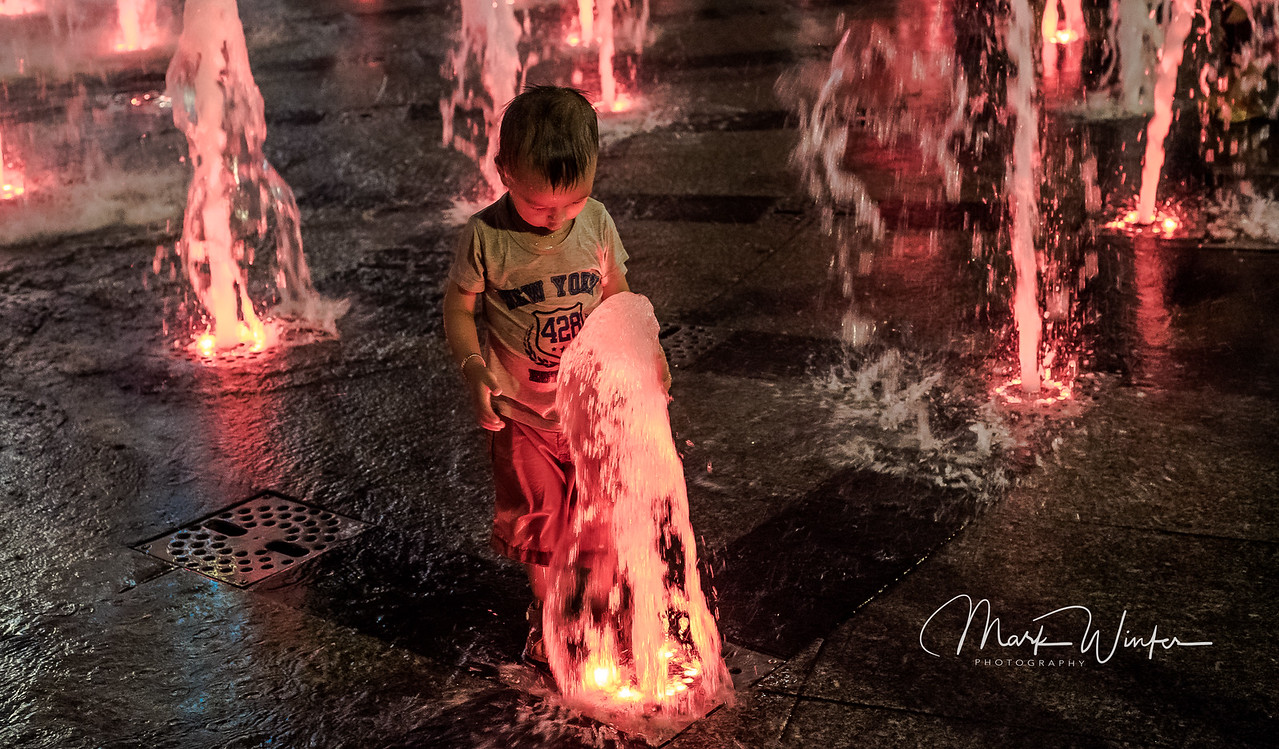 Saigon. Outside the former Presidential Residence, people stroll on a hot summer evening. Colored water fountains spring from the concrete and children walking by with their parents enjoy splashing in the pools.