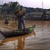Fisherman, Mekong River.  Boat looks hand hewn.