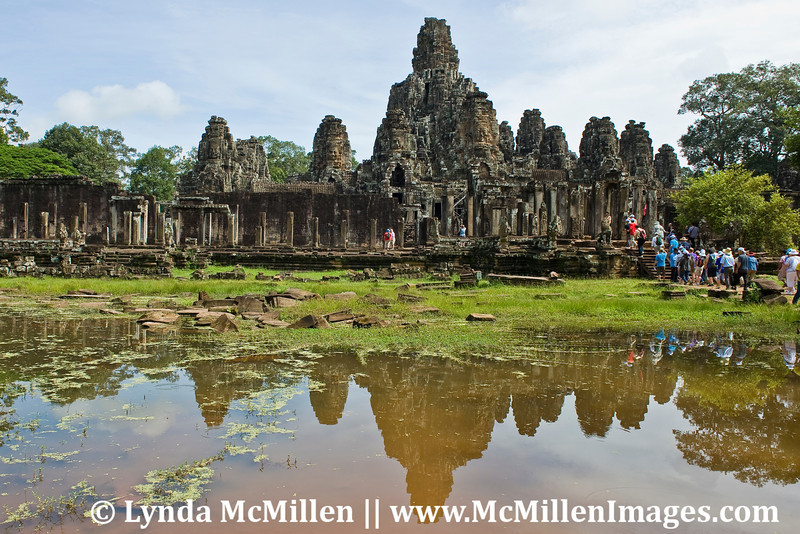 The Red Bus enters (see flag?) Bayon Temple adorned with 216 gigantic smiling faces.