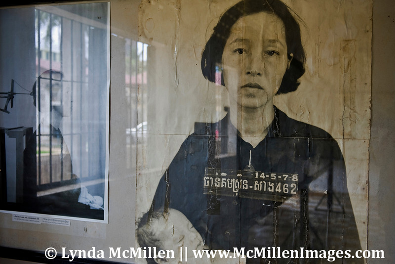 Using the prison's barred window reflection to add context to the pictured victim and her baby, both killed by the Khmer Rouge.