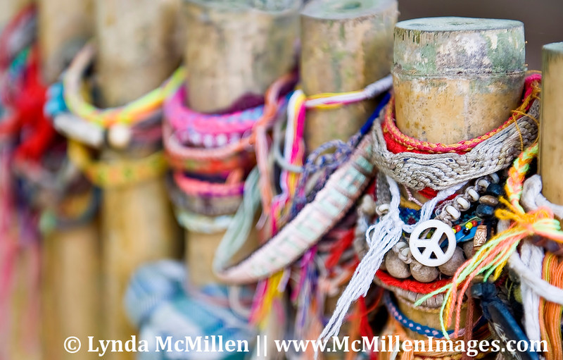 Amulets and colorful memorial bracelets are placed by local children to both honor the dead and to bring peace to their souls.