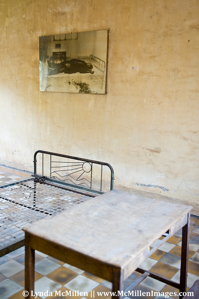 "A converted high school became the notorious S21 Khmer killing center: Here they held, tortured and eventually killed anyone with higher education who had ostensibly applied for jobs to ""help build Cambodia"". Pictured is an original interrogation room with table, bed and leg irons used to torture the victim pictured in the wall ""art""."