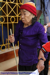 An elderly woman is assisted by her family and doctor after receiving a physical exam during a medical  mission to Vietnam