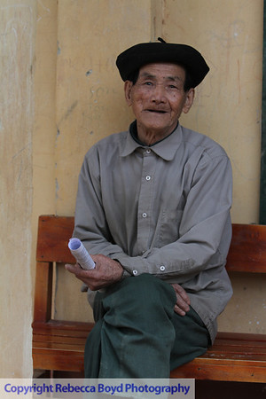 An elderly man waited for family members after receiving a physical exam during a medical  mission to Vietnam