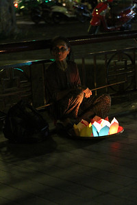 A woman sells paper lanterns on a bridge