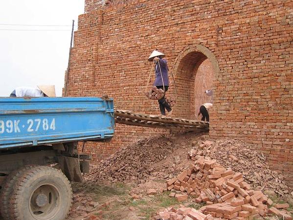 Kvinna släpar tegelstenar