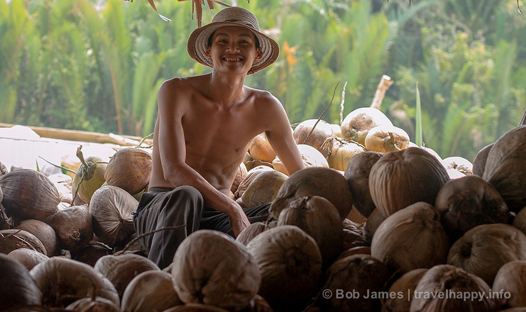At a Ben Tre coconut processing factory, a worker rests amid his pile of fruit to be peeled.