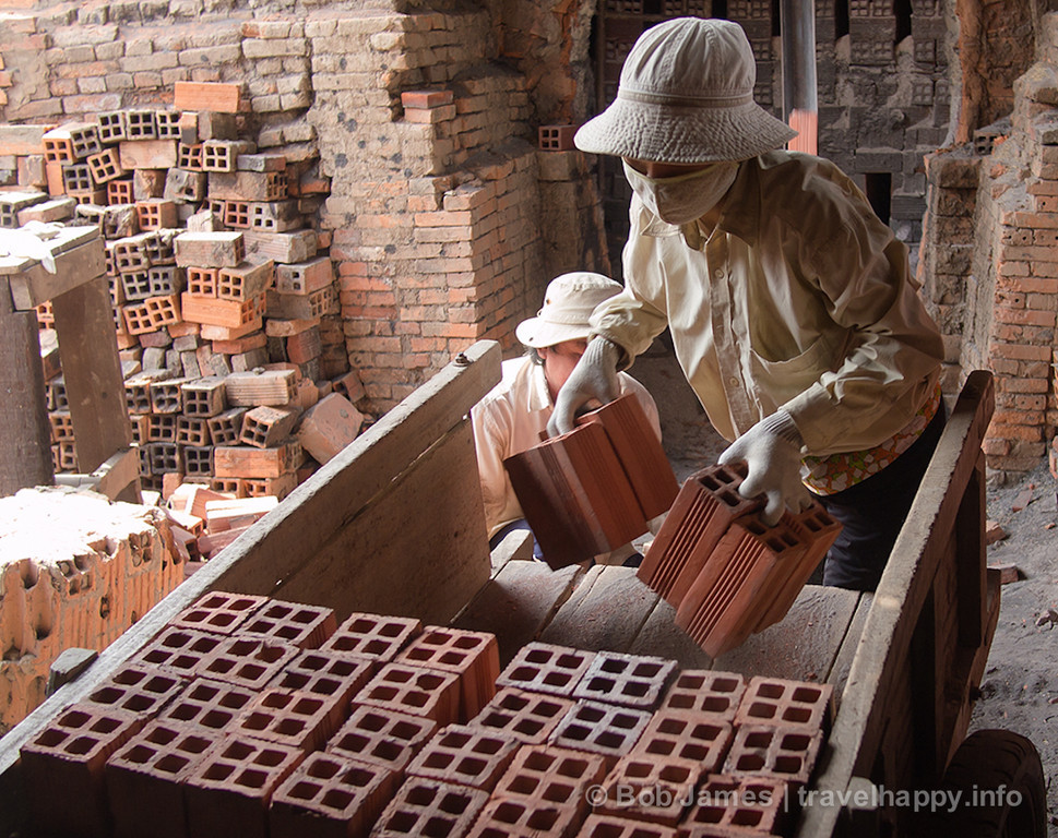 Women load bricks into a cart for shipment at a Ben Tre foundry.