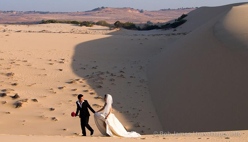 A Vietnamese couple uses Mui Ne's white-sand dunes as a backdrop for wedding photos.