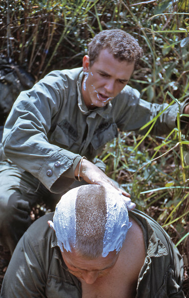 """Eat-Man"" giving Sgt. Williams a mohawk.  Entertainment was hard to come by out in the bush."