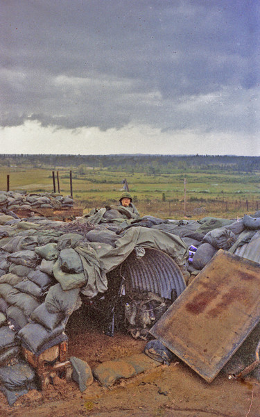 Roger Ashe at our bunker in the mud outside Chu Lai.  I shared the culvert half in the foreground with Sgt. Williams.  He carried the C-4 plastic explosives and det. cord with blasting caps.  He used the C-4 bag as his pillow.