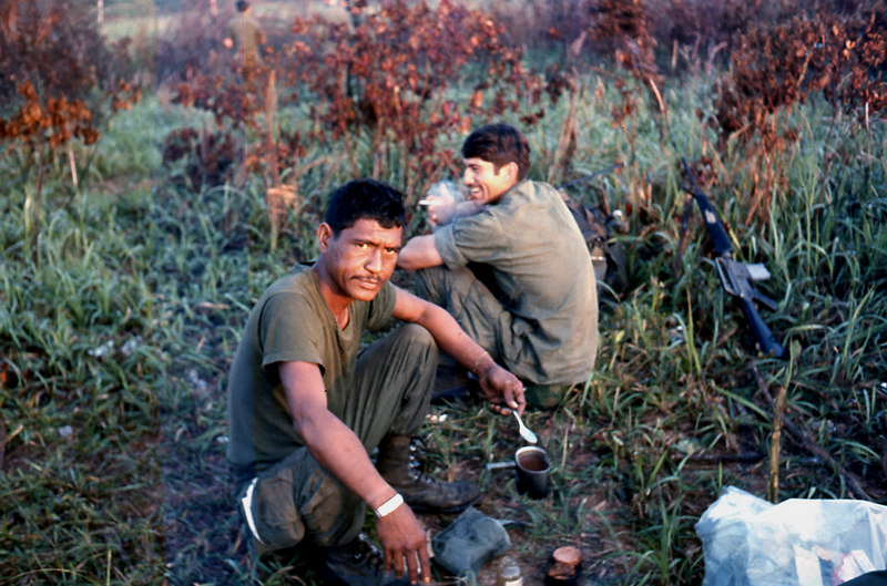 """Sgt. Duke at dinner.  Danny Vasquez behind him.  Sgt. Duke was Hawaiian and his Hawaiian name was too long for most of us to negotiate, so we just called him """"Duke"""".  He was the best platoon Sargeant out in the bush that any of us ever had.  As best as I can recall, his name was something like """"Kawaihalau"""".  Apologies, Duke, if I butchered it."""
