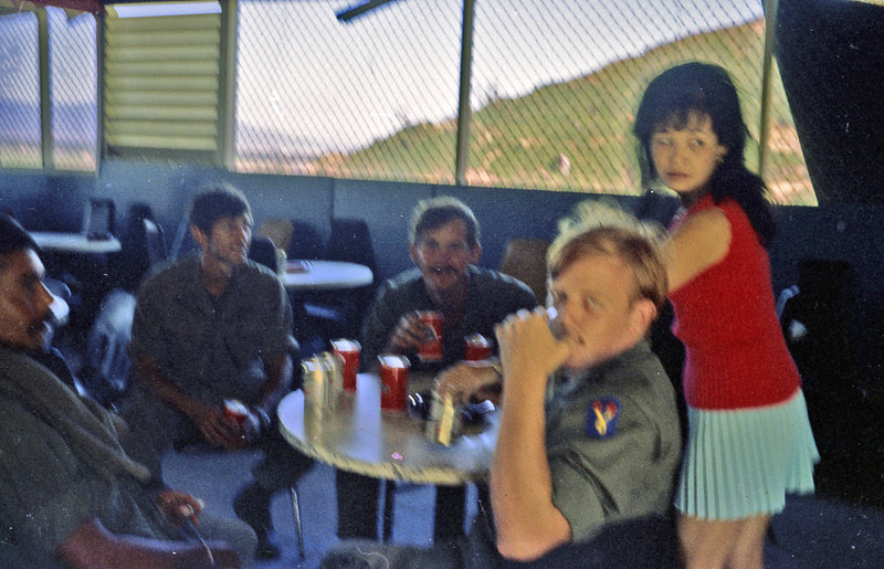 The 3/21 enlisted club.  It was on the side of a hill and had a great view of the outskirts of Da Nang.  Chavez, Vasquez, Evans and Sine with unknown bartender.  Picture is blurred because I had to grab it in a hurry.  Bartender was camera-shy.  Probably didn't want her mother to see her in that outfit.