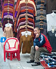 Shopkeeper sitting in front of his merchandise (clothes) in Hanoi, Vietnam in January 2012