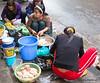 People preparing food on the sidewalk in Hanoi in January 2012