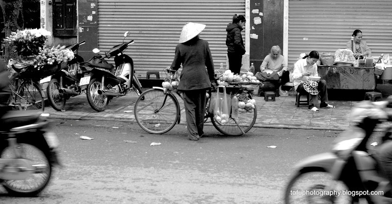 Woman with a bicycle in Hanoi, Vietnam in January 2012