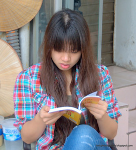 Pretty woman reading in Hanoi, Vietnam in January 2012