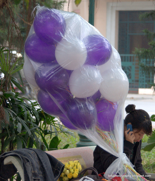 Woman with balloons at the Hoàn Kiếm Lake in Hanoi, Vietnam in January 2012