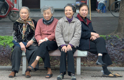 Four women relaxing on a park bench by the Hoàn Kiếm Lake in Hanoi, Vietnam in January 2012