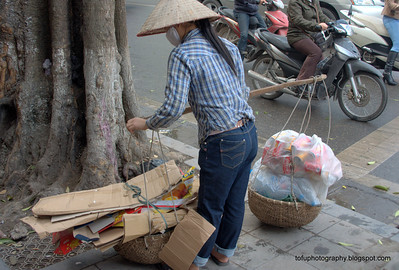 Woman collecting rubbish to sell for recycling in Hanoi, Vietnam in January 2012