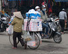 Woman with an overloaded bicycle in Hanoi, Vietnam in January 2012