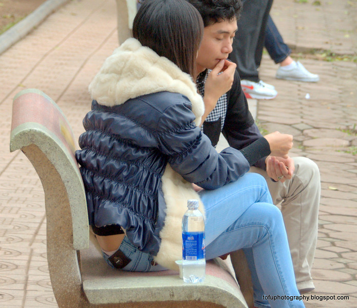 Couple on a park bench by the Hoàn Kiếm Lake in Hanoi, Vietnam in January 2012