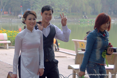 Wedding couple and a pretty woman at the Hoàn Kiếm Lake in Hanoi, Vietnam in January 2012