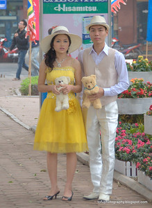Smartly dressed wedding couple at the Hoàn Kiếm Lake in Hanoi, Vietnam in January 2012
