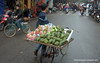 Man with a bicycle carrying fruit in Hanoi, Vietnam in January 2012