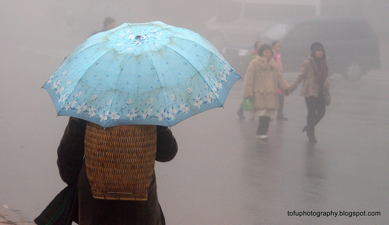 Local woman with a light blue umbrella and a basket on her back in a very foggy Sapa, Vietnam in January 2012
