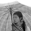 Cold woman sheltering under a large umbrella in Sapa, Vietnam in January 2012