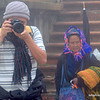 Woman in traditional dress and a man taking a photo in Sapa, Vietnam in January 2012