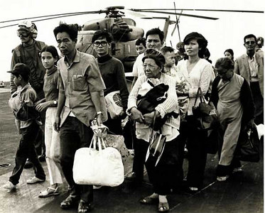 South Vietnamese refugees walk across a U.S. Navy vessel. Operation Frequent Wind, the final operation in Saigon, began April 29, 1975. During a nearly constant barrage of explosions, the Marines loaded American and Vietnamese civilians, who feared for their lives, onto helicopters that brought them to waiting aircraft carriers. The Navy vessels brought them to the Philippines and eventually to Camp Pendleton, CA.