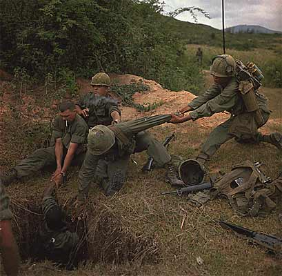 """Operation """"Oregon,"""" a search and destroy mission conducted by infantry platoon of Troop B. An infantryman is lowered into a tunnel by members of the reconnaissance platoon, April 24, 1967."""