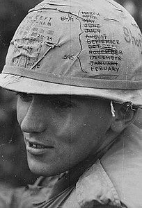 "A sky trooper from the 1st Cavalry Division keeps track of the time he has left on his ""short time"" helmet, 1968."