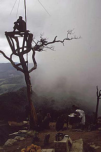 A Marine stands watch in an observation tower as a chaplain holds mass on Hill 950, July 31, 1967.
