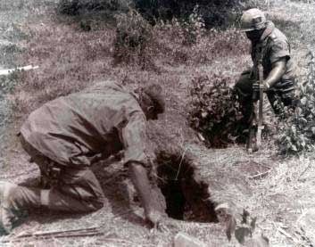 A soldier from the 8th Engineer Battalion, 1st Cavalry Division prepares to enter a tunnel while an armed soldier keeps guard. They were hoping to clear any Viet Cong who might be hiding in the tunnel out.