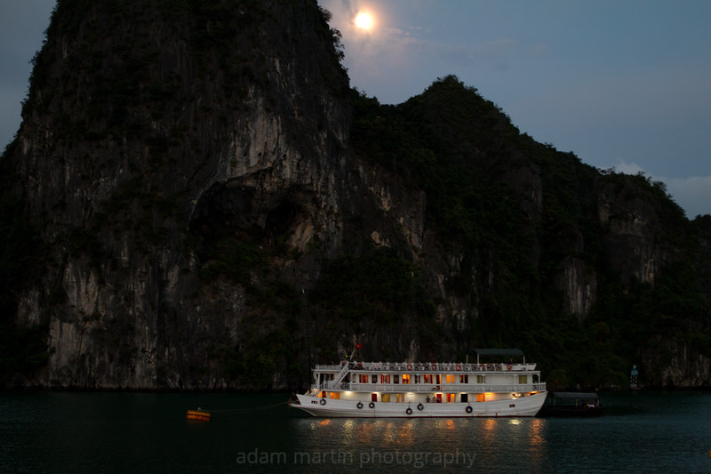 A boat and a mooring buoy, an island and a moon. Halong Bay Vietnam