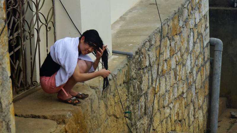 Today's daily feature travel picture is of a Vietnamese lady rinsing off her long hair in the gutter along a quiet street nearby my hotel in Sapa, Vietnam.