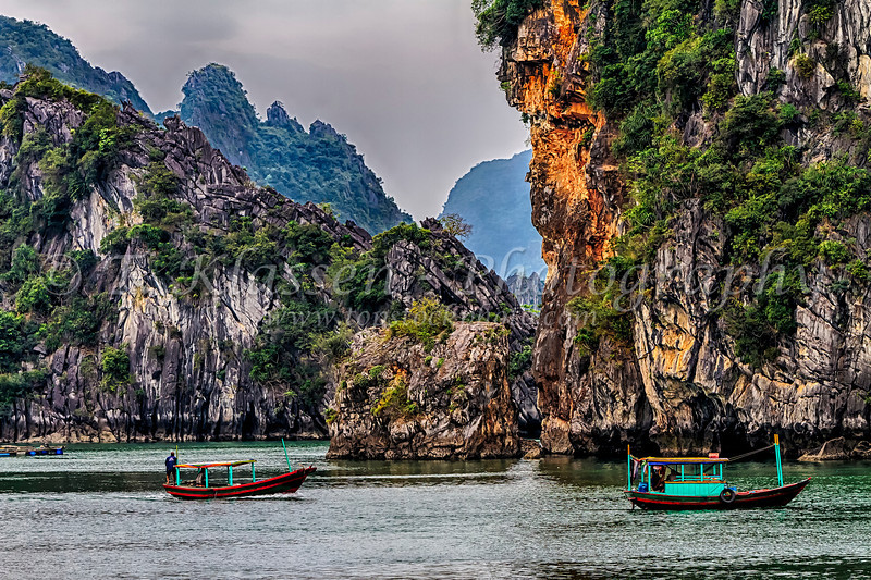Fishing boats among the limestone karsts and small islands in Ha Long Bay, Vietnam, Asia.