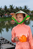 A young girl selling floating candles near the Japanese Bridge in Hoi An, Vietnam, Asia.