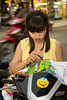 A young lady on a motorbike performing embroidery on the street in Hanoi, Vietnam, Asia.