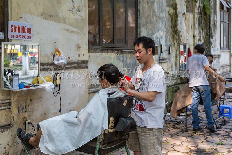 An on the street hair dressing salon in Hanoi, Vietnam, Asia.