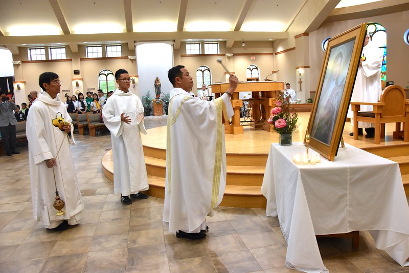 Fr. Joseph Quang blesses the image of St. Theresa