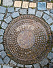 Manhole cover and donated cobblestones on a walk in Cesky Krumlov