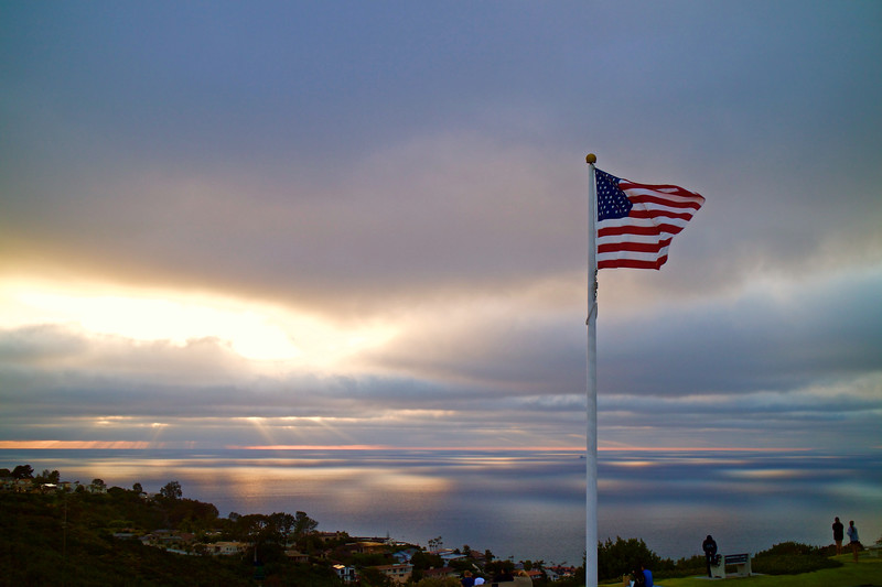 The sun sets behind the flag flying over a veterans memorial on the anniversary of D-Day.