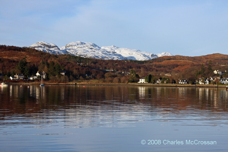 View up Gareloch to village of Garelochhead and snow capped mountains in background