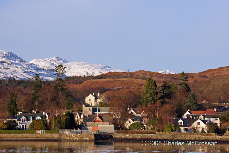 View up Gareloch to village of Garelochhead and snow capped mountains in background - train passing over viaduct above town
