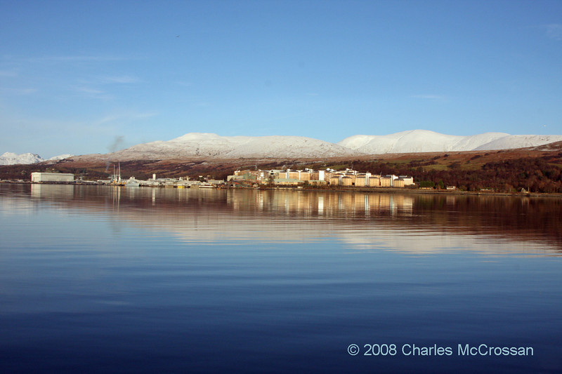 View up Gareloch to snow capped mountains with Faslane base in foreground