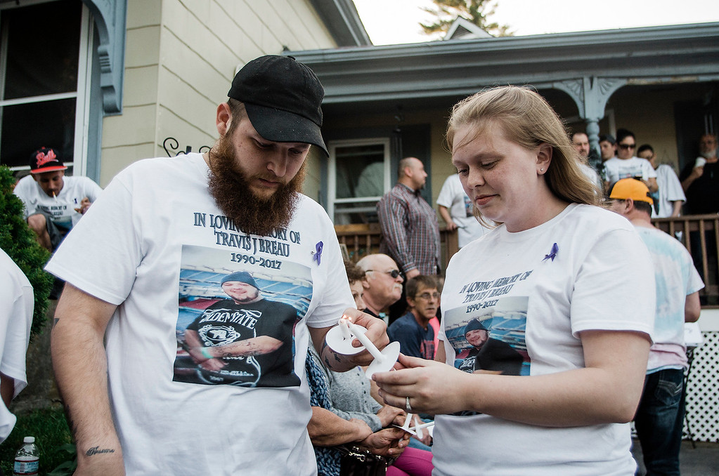 . Jacob Breau, the brother of Travis Breau, who died of a drug overdose in early May, along with Kari-Ann Pugsley, light candles during the vigil held in his honor on Friday, May 19, 2017. SENTINEL & ENTERPRISE / Ashley Green